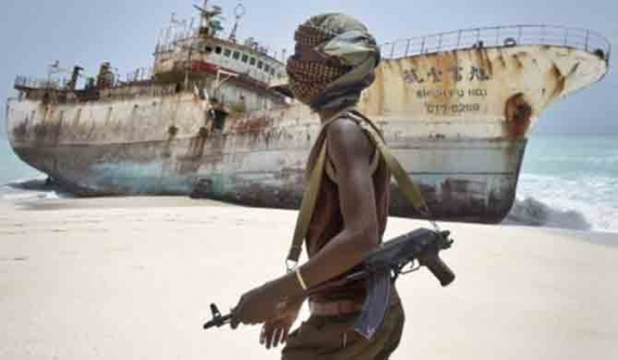 In this photo taken Sunday, Sept. 23, 2012, masked Somali pirate Abdi Ali walks past a Taiwanese fishing vessel that washed up on shore after the pirates were paid a ransom and released the crew, in the once-bustling pirate den of Hobyo, Somalia. Farah Abdi Warsameh / AP