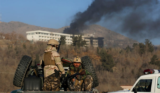 Afghan security forces keep watch as smoke rises from the Intercontinental Hotel in Kabul, Afghanistan after the Taliban attacked. Photo by REUTERS/Omar Sobhani.